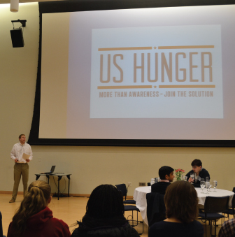 Students sit at tables, while a presenter discusses hunger in the US