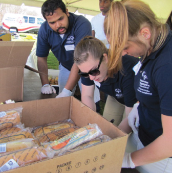 A group of students sort sandwiches for a volunteer lunch