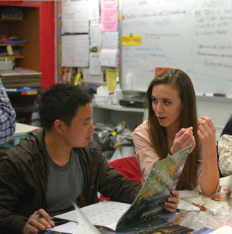 Two students engage in a conversation about service